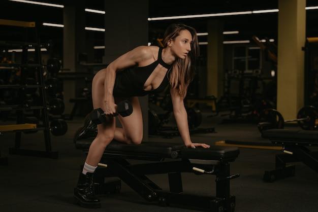 Wysportowana brunetka robi jednoręki wiosłowanie hantlami z kolanem na ławce. umięśniona dziewczyna nosi czarne stringi i buty podczas treningu pleców na siłowni.