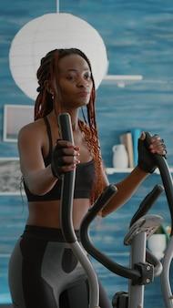 Wysportowana czarna kobieta biegająca na rowerze eliptycznym oglądając rutynę wellness