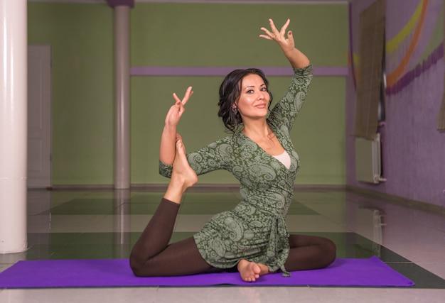 Wysportowana dziewczyna ćwiczy lekcję jogi w studio