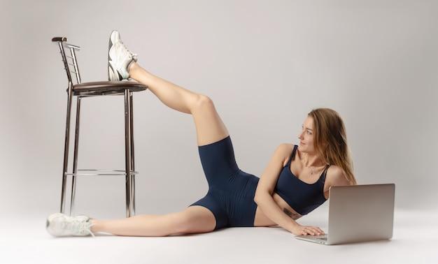 Wysportowana dziewczyna pozuje w studio wykonując ćwiczenia online na laptopie na białym tle