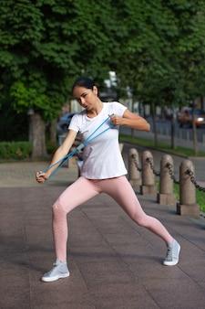 Wysportowana dziewczyna rozciągająca się w parku z niebieską opaską oporową