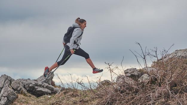 Wysportowana dziewczyna skacze między kamieniami podczas alpejskiego trekkingu
