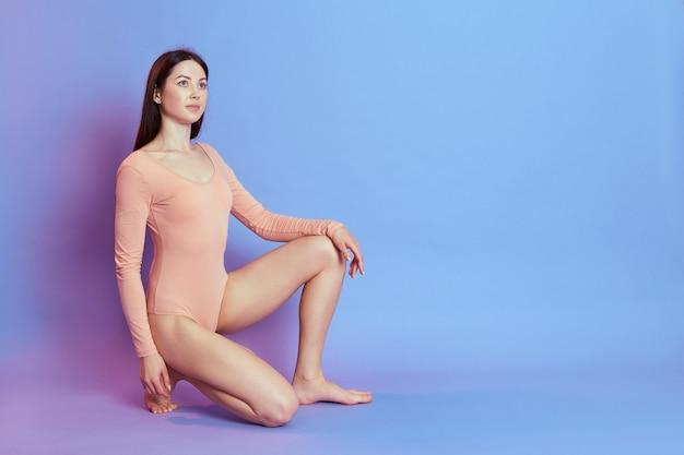 Wysportowana dziewczyna ubrana w beżowe body, siedząca na jednym kolanie odizolowana na niebieskiej ścianie z różowym neonowym światłem, kobieta o idealnej sylwetce. sport, fitness, dieta i opieka zdrowotna.