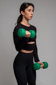 Wysportowana dziewczyna wykonująca uginanie hantli na biceps na szarej powierzchni