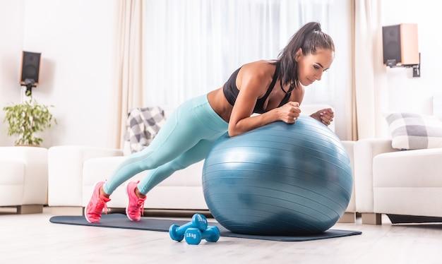Wysportowana dziewczyna wykonuje deskę na piłce fit podczas treningu w domu z hantlem na boku.
