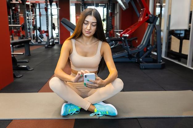 Wysportowana dziewczyna ze smartfonem siedzi na macie
