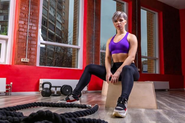 Wysportowana i szczęśliwa młoda blondynka pozuje z atheltic treningowymi linami na siłowni