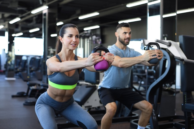 Wysportowana i umięśniona para skupiona na podnoszeniu hantli podczas ćwiczeń na siłowni.