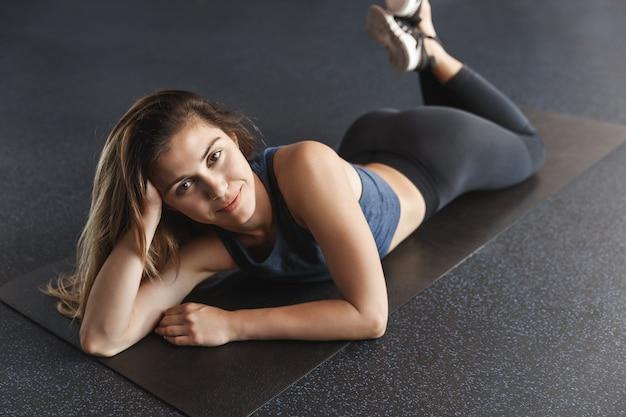 Wysportowana i zdrowa, atrakcyjna młoda kobieta w dobrej kondycji, lekkoatletka leżąca na gumowej macie.