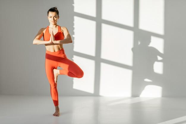 Wysportowana kobieta balansująca w pozie jogi w pomieszczeniu