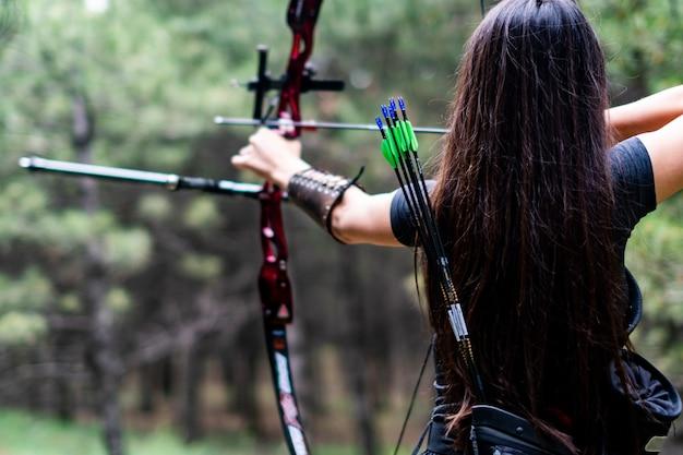 Wysportowana kobieta celująca łukiem i strzałą w kierunku drzew