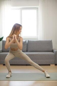 Wysportowana kobieta ćwicząca i trenująca w domu at