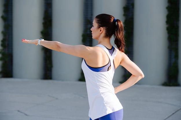 Wysportowana kobieta ćwicząca na betonowych słupach podporowych z tyłu