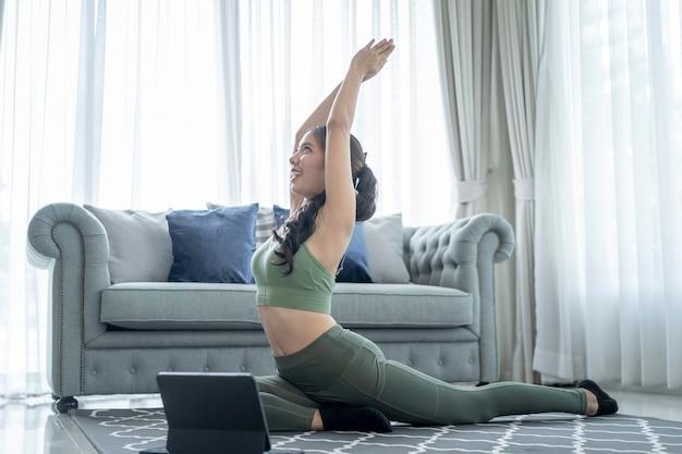 Wysportowana kobieta ćwicząca w stroju sportowym podczas oglądania sesji ćwiczeń online na swoim tablecie w domu