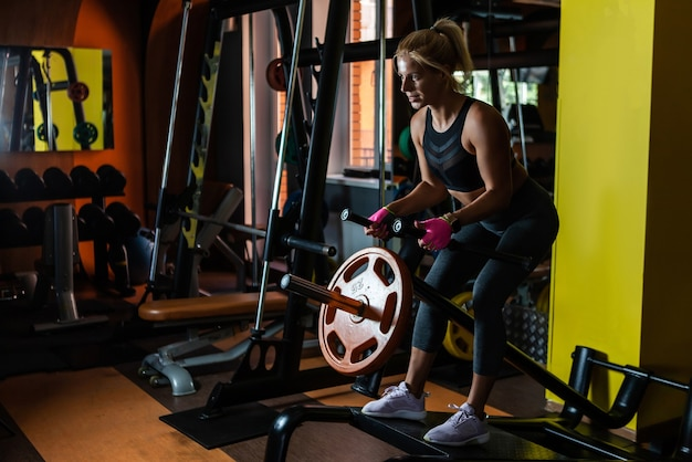 Wysportowana kobieta ćwiczy na siłowni, korzystając z treningu wioślarstwa na plecach