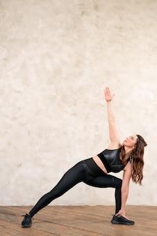 Wysportowana kobieta ćwiczy na tle ściany rozciąganie miejsca na tekst