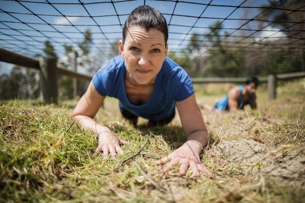 Wysportowana kobieta czołgająca się pod siatką podczas toru przeszkód w obozie treningowym