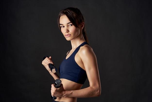 Wysportowana kobieta hantle do ćwiczeń fitness w rękach silnego izolowanego tła