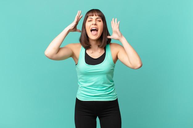Wysportowana kobieta krzycząca z rękami w górze, wściekła, sfrustrowana, zestresowana i zdenerwowana