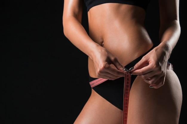 Wysportowana kobieta mierząca idealny kształt pięknej sylwetki. zdrowy styl życia i koncepcja fitness