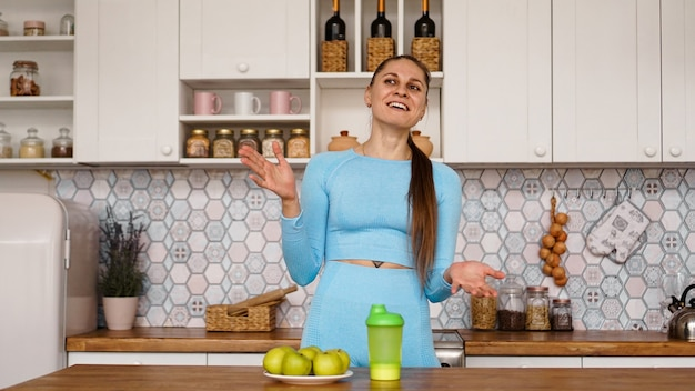 Wysportowana kobieta mówi o zdrowym odżywianiu w kuchni i się śmieje. na stole są zielone jabłka i zielona butelka na sportowy napój i wodę