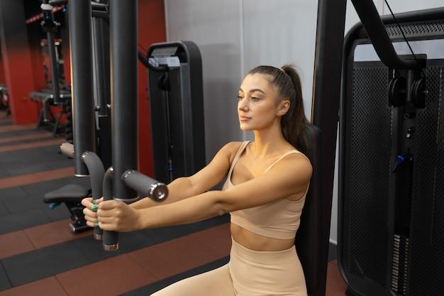 Wysportowana kobieta na siłowni na symulatorze motyla