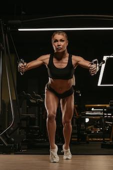 Wysportowana kobieta o blond włosach ćwiczy klatkę piersiową na kablówce w siłowni. dziewczyna ćwiczy mięśnie piersiowe.