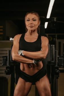 Wysportowana kobieta o blond włosach pozuje z rękami skrzyżowanymi na siłowni