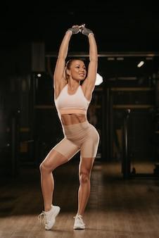 Wysportowana kobieta o blond włosach rozciąga się z rękami do góry na siłowni
