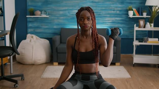 Wysportowana kobieta o ciemnej skórze wykonująca ćwiczenia z hantlami fitness, siedząca na piłce szwajcarskiej