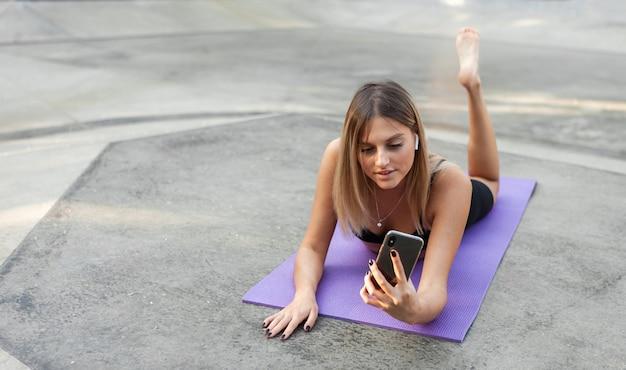 Wysportowana kobieta odpoczywa na świeżym powietrzu po treningu i używa smartfona