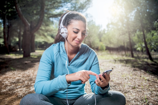 Wysportowana kobieta przed rozpoczęciem konfigurowania aplikacji na smartfona, koncepcja fitness