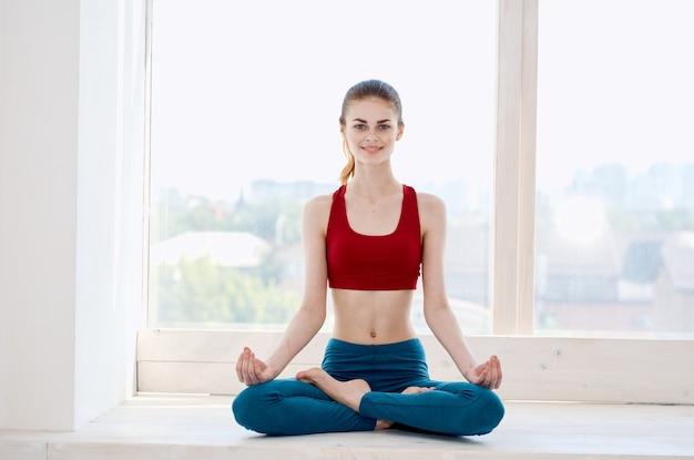 Wysportowana kobieta robi asanę ćwiczeń jogi w pobliżu okna