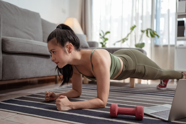 Wysportowana kobieta robi deskę do jogi i ogląda samouczki online na treningu na laptopie w salonie