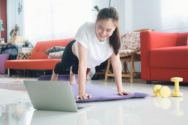 Wysportowana kobieta robi deskę do jogi i ogląda tutoriale online, trenuje w salonie. zostań w domu.