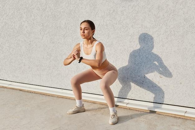 Wysportowana kobieta robi przysiady rozgrzewające, rozciąga się w pobliżu szarej ściany