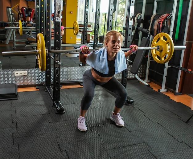 Wysportowana kobieta robi przysiady ze sztangą na siłowni
