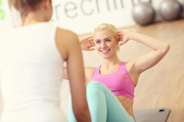 Wysportowana kobieta robi siady na siłowni