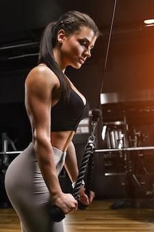 Wysportowana kobieta robi triceps w bloku, ćwiczenia rąk dziewczyna w wygodnym dresie, ma smukłą, atletyczną sylwetkę, mocne, zdrowe ciało