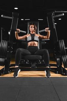 Wysportowana Kobieta Robi Triceps W Bloku, ćwiczenia Rąk Dziewczyna W Wygodnym Dresie, Ma Smukłą, Atletyczną Sylwetkę, Mocne, Zdrowe Ciało Premium Zdjęcia