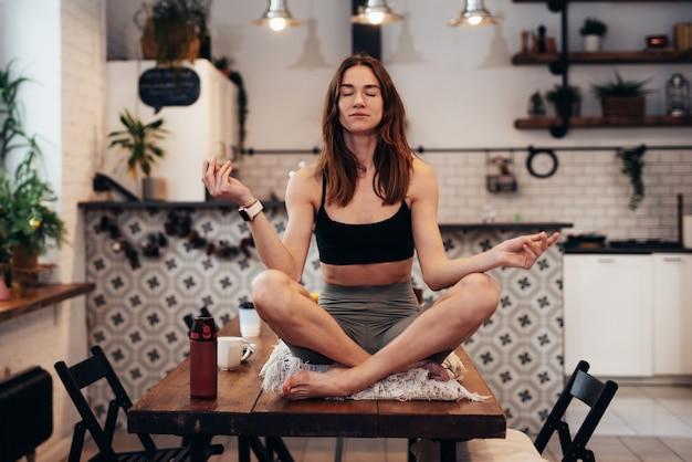 Wysportowana kobieta siedzi na stole z zamkniętymi oczami i medytuje.