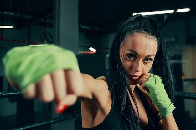 Wysportowana kobieta stojąca przygotowana do walki z bandażami bokserskimi na rękach podczas treningu bokserskiego