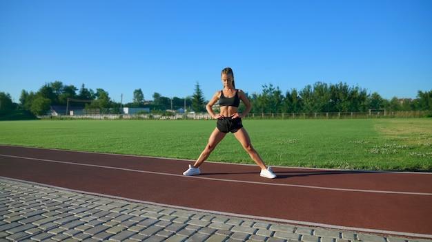 Wysportowana kobieta trenująca na stadionie na świeżym powietrzu