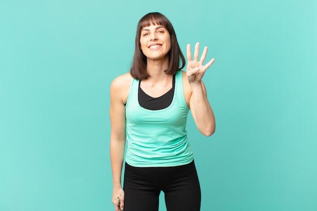 Wysportowana kobieta uśmiechnięta i wyglądająca przyjaźnie, pokazująca cyfrę cztery lub czwartą z ręką do przodu, odliczając w dół