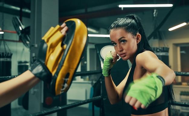 Wysportowana kobieta w akcji z bandażami bokserskimi na rękach podczas treningu bokserskiego