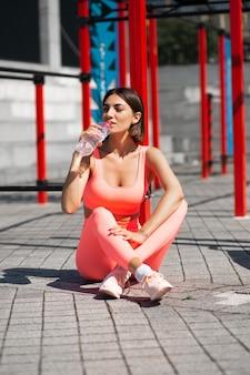 Wysportowana kobieta w różowej dopasowanej odzieży sportowej na świeżym powietrzu z butelką wody