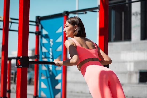 Wysportowana kobieta w różowej dopasowanej stroju sportowym na zewnątrz robi pompki na barze