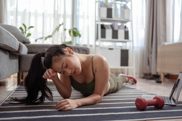 Wysportowana kobieta w stroju sportowym odpoczywa na podłodze z hantlami i korzysta w domu z laptopa