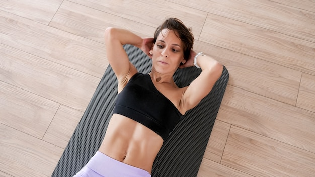 Wysportowana kobieta w stroju sportowym pompuje mięśnie brzucha. ona robi ćwiczenia abs na macie w siłowni. koncepcja sportu i fitness.