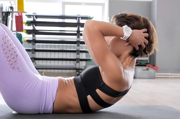 Wysportowana kobieta w stroju sportowym pompuje mięśnie brzucha. ona robi ćwiczenia abs na macie w siłowni, widok z boku. koncepcja sportu i fitness.
